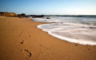Ocean Surge Beach & Foot Steps wallpapers and stock photos