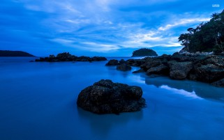 Deep Blue Water Black Rocks wallpapers and stock photos